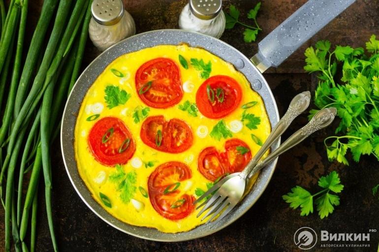 Омлет с помидорами и зеленью на сковороде