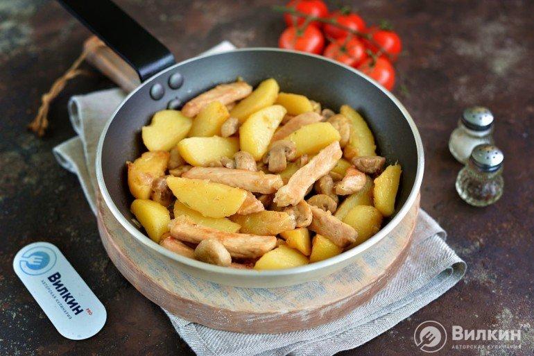 порция жареного картофеля со свининой и грибами