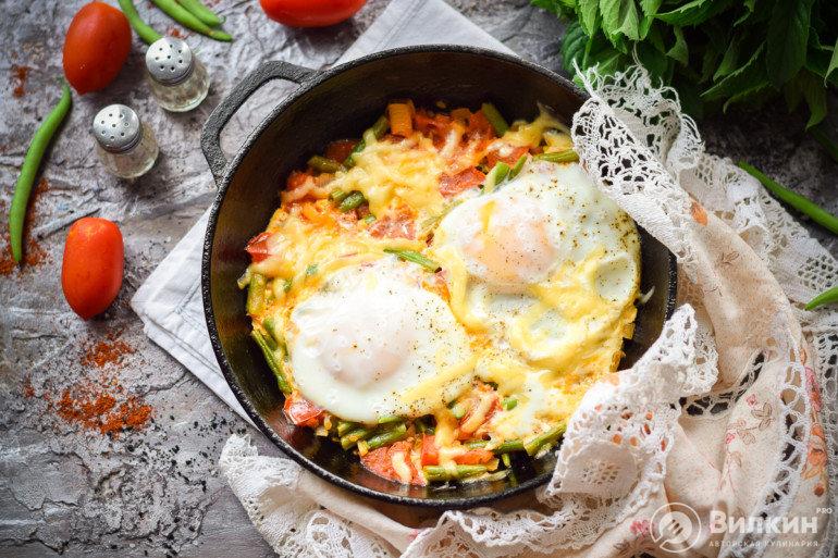 Зеленая стручковая фасоль с яйцом, помидором и чесноком на сковороде