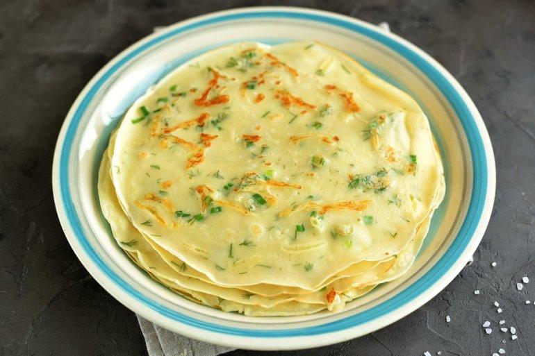 стопка блинов с сыром и зеленью