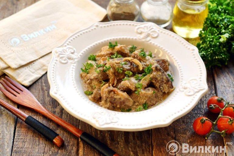 порция говяжьей печени с луком в сметанном соусе