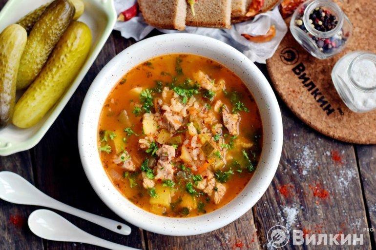 Порция супа с рисом и солеными огурцами