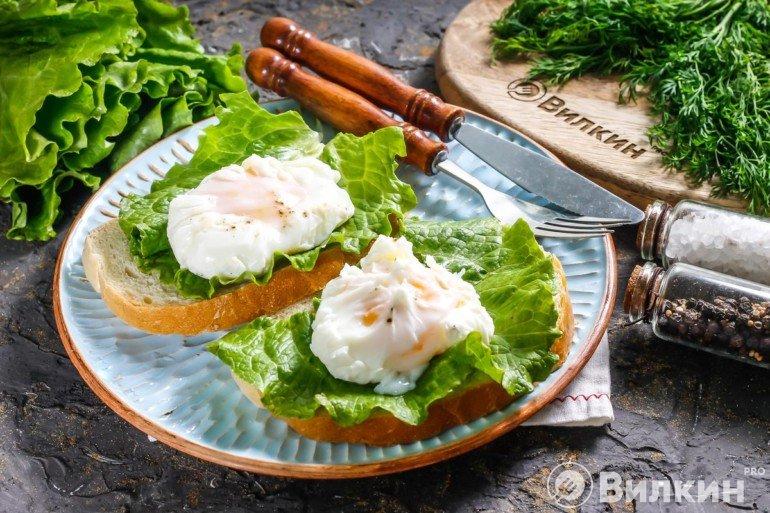 Выкладка готовых яиц на хлеб с салатными листьями