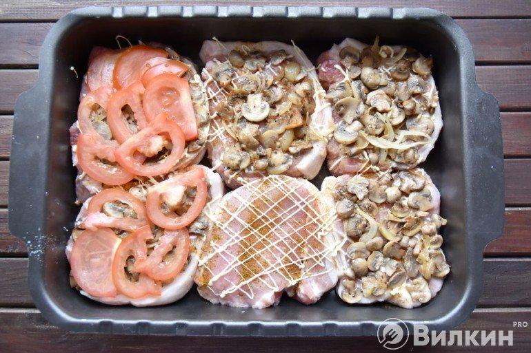 Выкладка грибов и помидоров на мясо