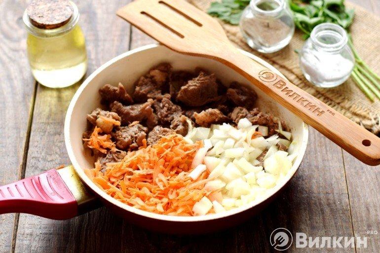 Добавление лука и моркови к мясу