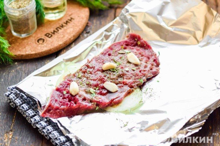 Кусок мяса на фольге